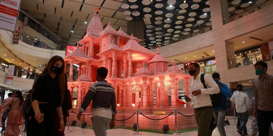 Visitors pass by Ayodhya's Ram Temple model in background at the Pacific Mall in Tagore Garden