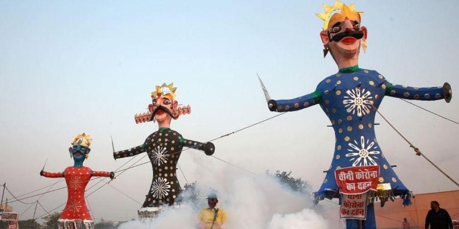 Municipal Corporation worker fumigate near the effigies of demon king Ravana Meghnad and brother Kumbhkaran installed ahead of Dussehra festival in New Delhi