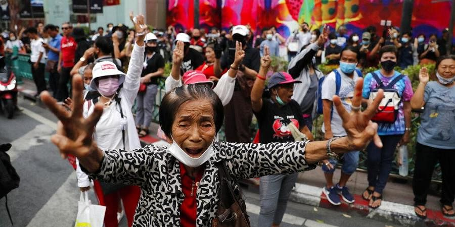 Pro-democracy protesters gather, flashing three-fingered salutes near a main shopping district in Bangkok, Thailand, Sunday, Oct. 25, 2020.