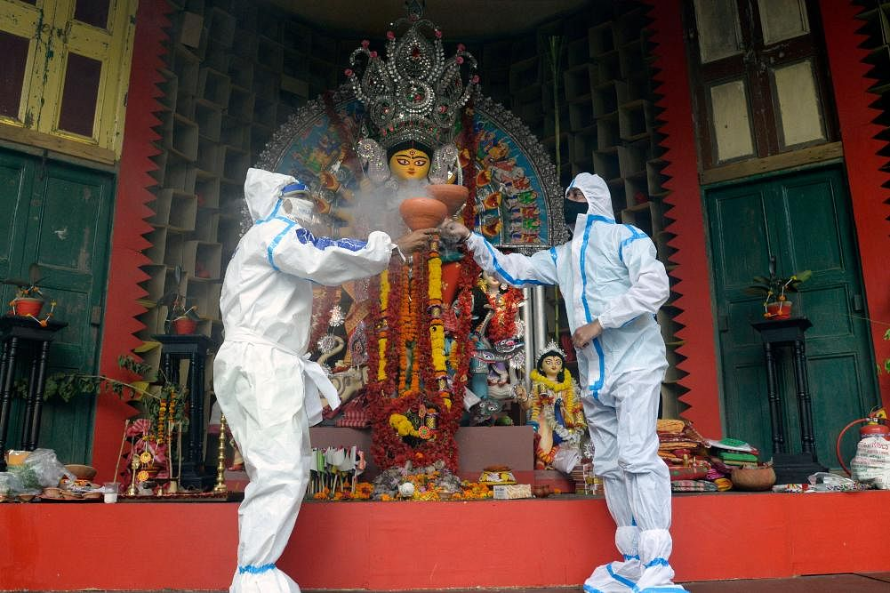 Devotees wearing PPE kits perform the traditional 'Dhunuchi dance' in front of an idol during Durga Puja in Kolkata