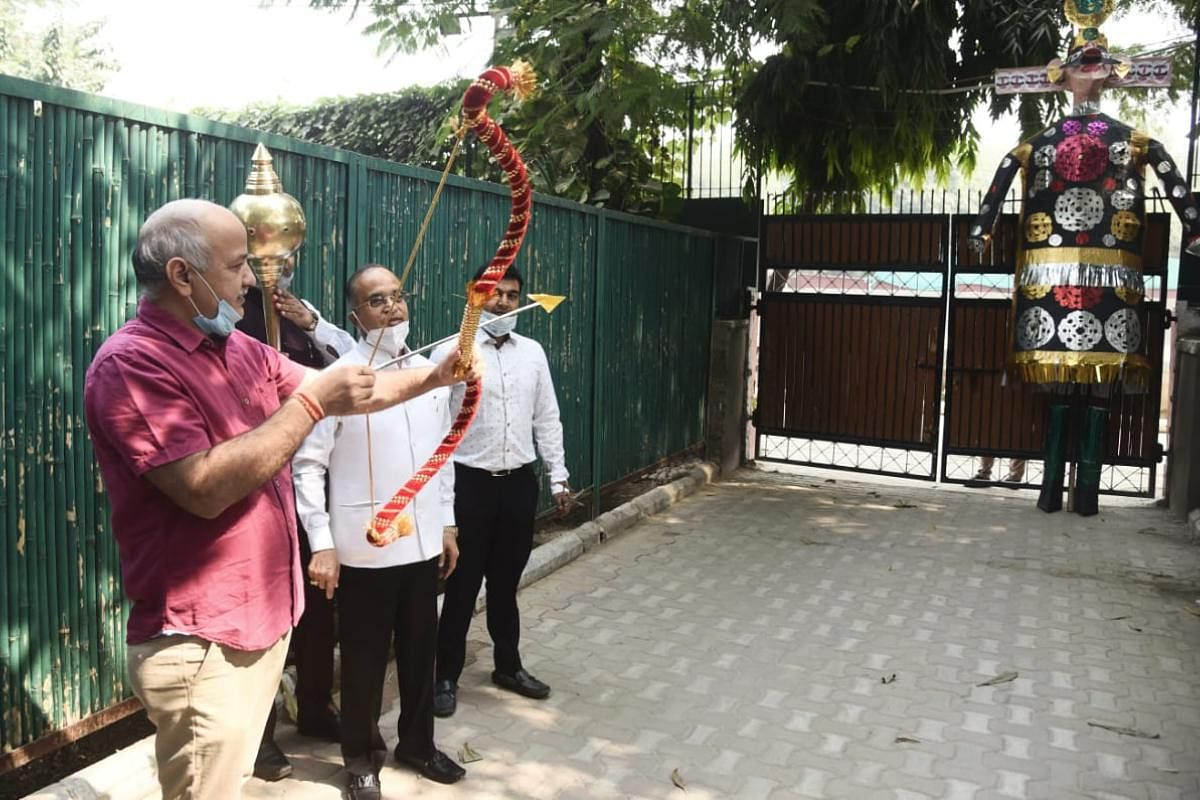 Delhi Deputy Chief Minister Manish Sisodia releases the arrow with a bow towards an effigy of Ravana during Dussehra celebrations at his residence