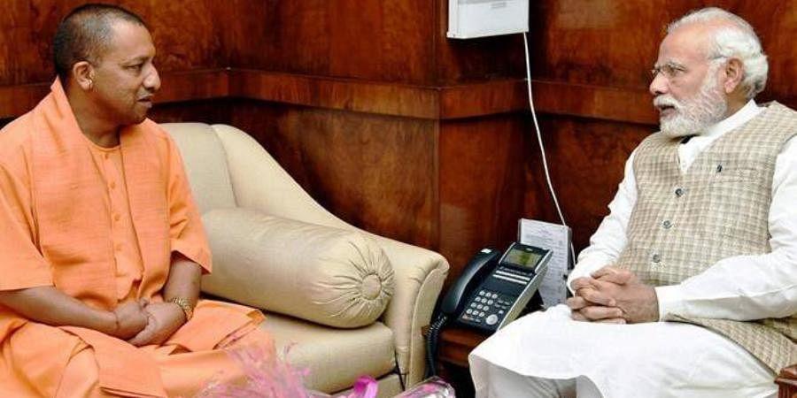 PM Narendra Modi (R) with Uttar Pradesh CM Yogi Adityanath