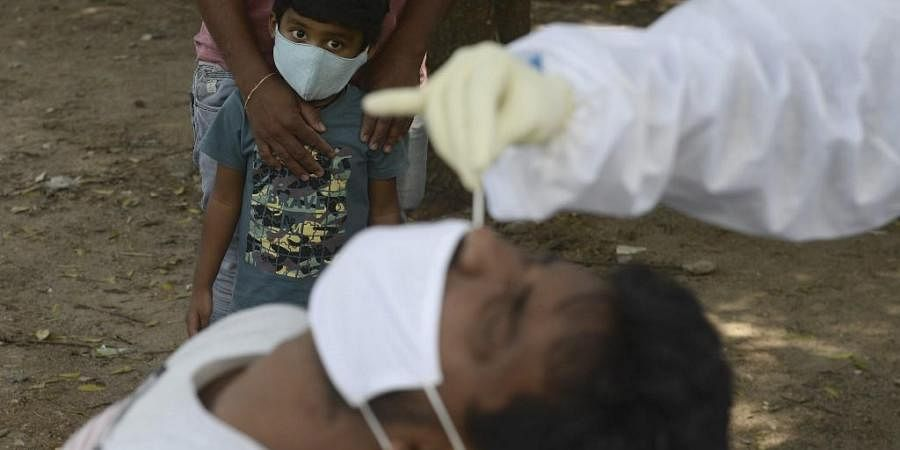 A boy watches as a health worker collects a swab sample from a man to test for the Covid-19 coronavirus. (Photo| AFP)