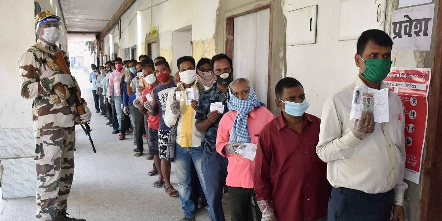 People stand in a queue to cast their votes during the first phase of Bihar Assembly polls amid the ongoing coronavirus pandemic in Gaya.