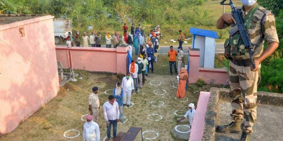 Voters, adhering to social distancing norms, stand in a queue to cast their votes for the first phase of Bihar Assembly Election