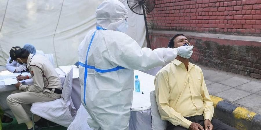 A health worker collects swab samples for COVID-19 tests at Saroijni Nagar Market in New Delhi Thursday