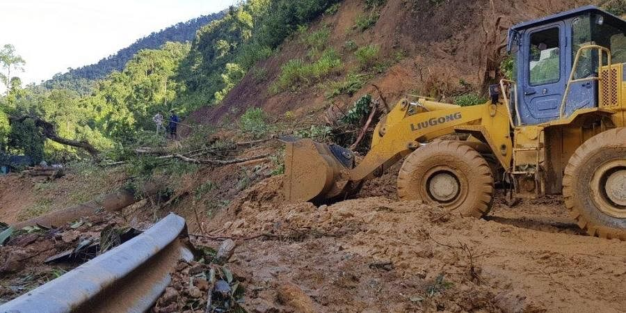 A bulldozer clears out the road damaged by landslide to access a village swamped by another landslide in Quang Nam province, Vietnam on Thursday, Oct. 29, 2020. (Photo | AP)