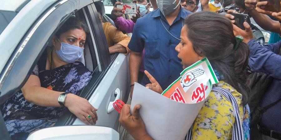 A Congress party activist protests near the vehicle of Union Minister Smriti Irani. (Photo| PTI)