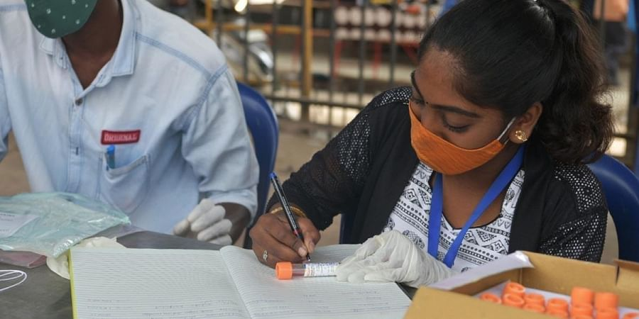 Staff at a Bengaluru fever clinic collect and label samples.