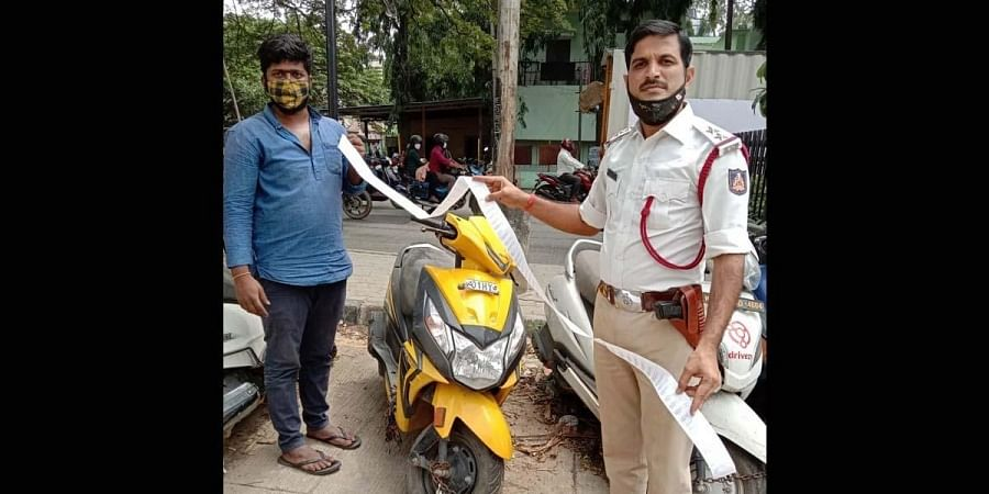 An officer with the seized scooter and the list of pending violation cases.