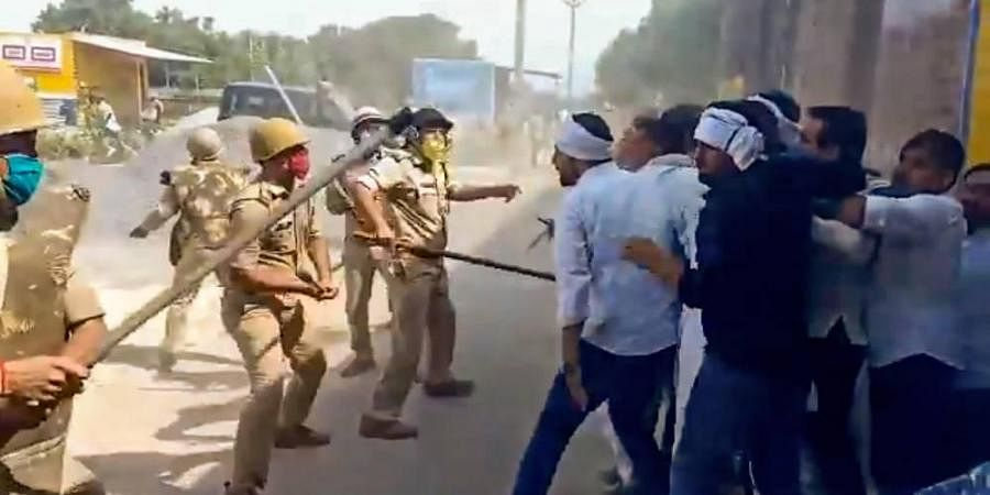 Police personnel baton charge on RLD leader Jayant Chaudhary and party workers during their visit to Hathras to meet the family members of a 19-year-old Dalit woman who was allegedly gang-raped two weeks ago