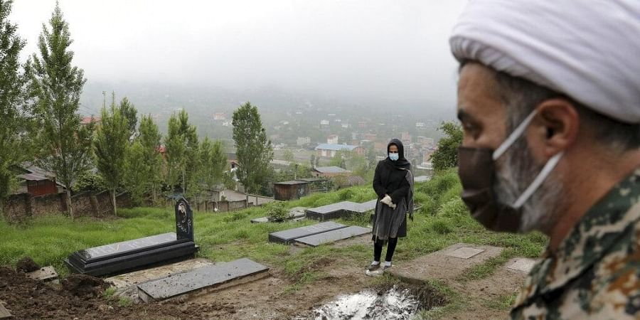 In this April 30, 2020 file photo, a woman wearing mask and gloves, prays at the grave of her mother who died from the new coronavirus, at a cemetery in the outskirts of Babol, Iran. (Photo | AP)