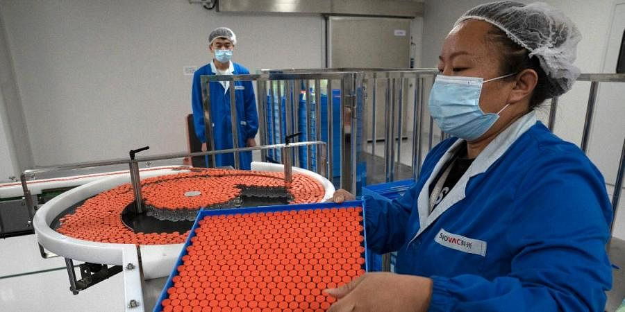 A worker feeds vials for production of SARS CoV-2 Vaccine for COVID-19 at the SinoVac vaccine factory in Beijing