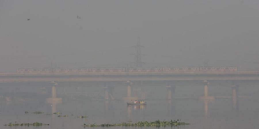 A boatman rows his boat on the Yamuna river amid heavy fog and smog conditions in New Delhi on Saturday. (Photo | Shekhar Yadav, EPS)