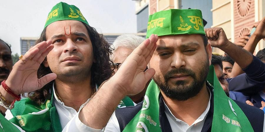 RJD leaders Tejashwi Yadav (front) and Tej Pratap wearing party caps during the open session of Rashtriya Janata Dal at Bapu Sabhagar in Patna Tuesday Dec. 10 2019. (Photo | PTI)