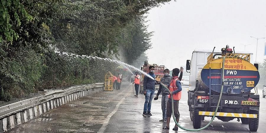 PWD workers spray water on trees to reduce dust near Raj Ghat Bus Depot during the vist of AAP's Gopal Rai.