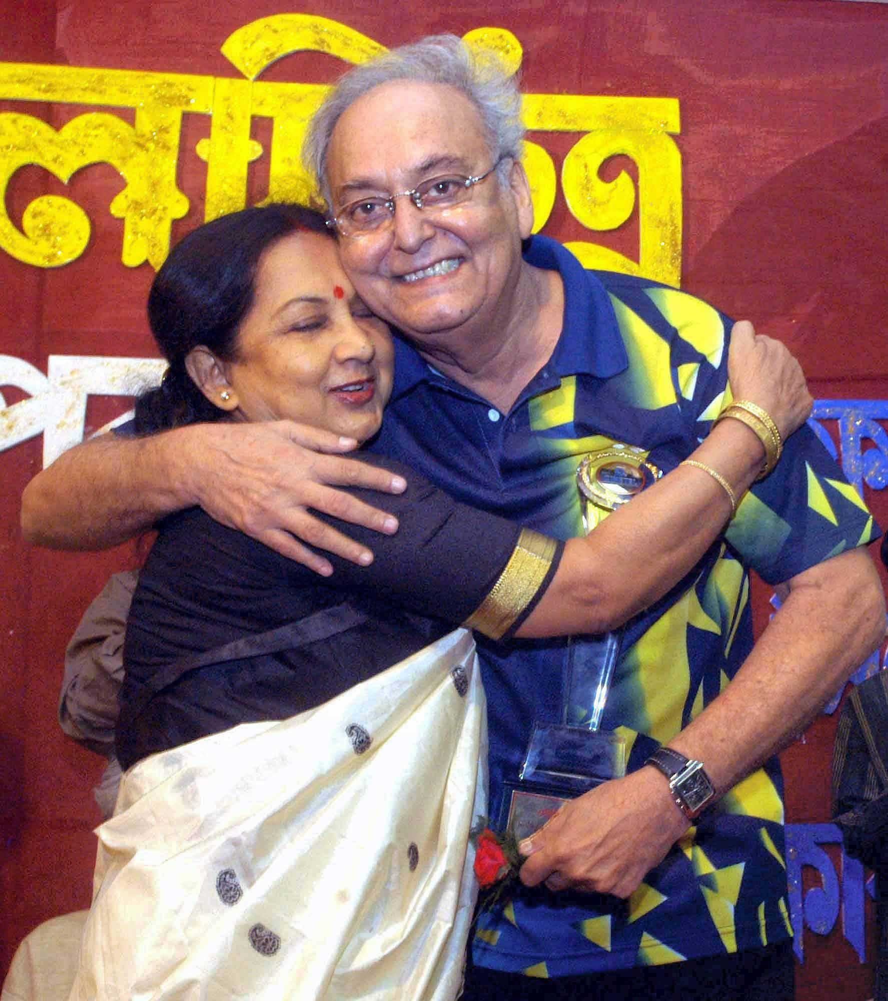 Bengali actress Sandhya Roy (L) hugs National Award winner Soumitra Chatterjee (R) during a felicitation ceremony, in Kolkata.
