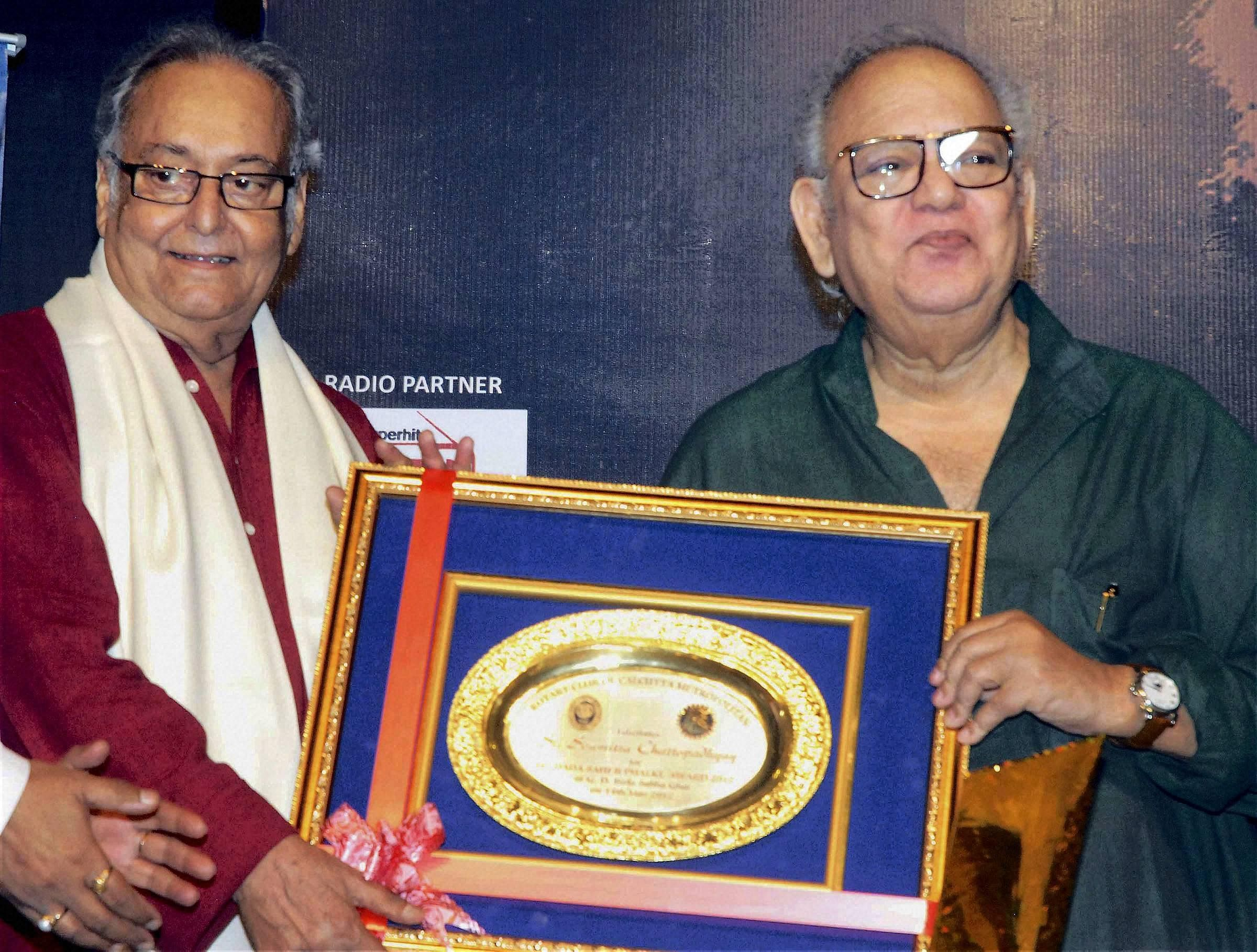 Veteran actor Soumitra Chatterjee being conferred with Lifetime Achievement Award by noted writer Buddhadeb Guha for his contribution to Indian cinema and theatre during his felicitation function in Kolkata.