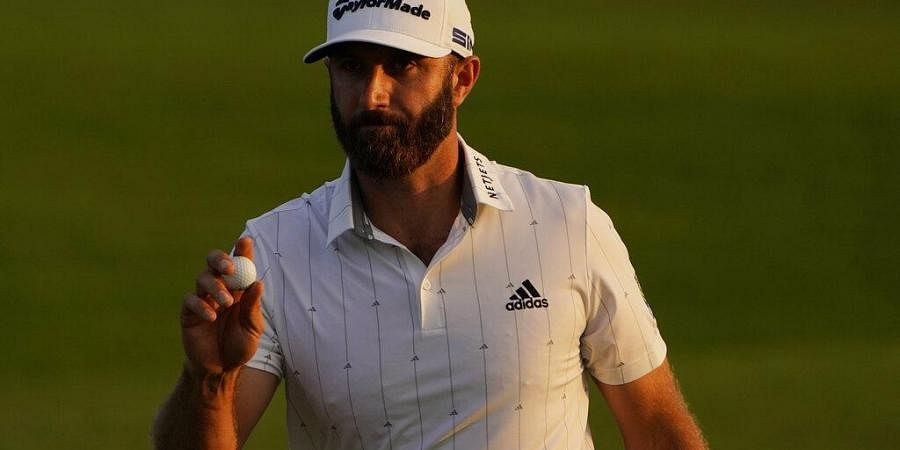 Dustin Johnson holds up his ball on the 18th green after his third round of the Masters golf tournament Saturday