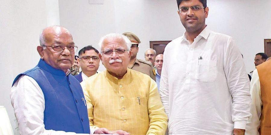 Haryana Chief Minister Manohar Lal Khattar with JJP chief Dushyant Chautala meets Governor Satyadeo Narain Arya. (File photo| PTI)