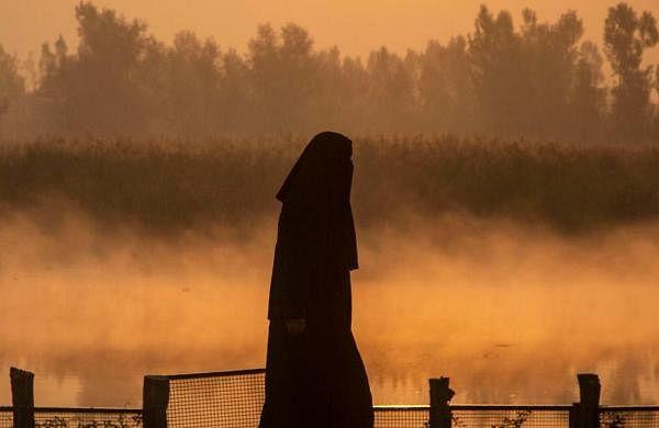 A Kashmiri woman walks in a cold morning on the banks of Babdemb Lake in Srinagar.