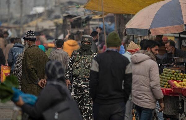 A paramilitary soldier patrols a crowded street in Srinagar.