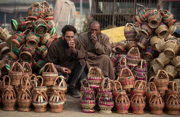 Kashmiri vendors drink tea as they wait for customers to sell Kangri, a traditional fire-pot, in Srinagar.