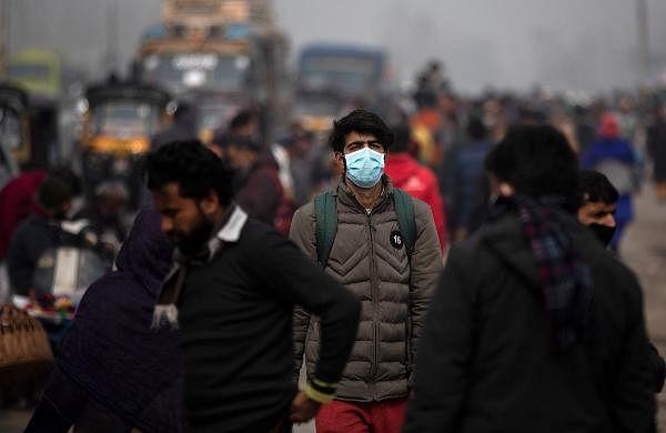 A Kashmiri man wearing a face mask walks on a crowded street in Srinagar.