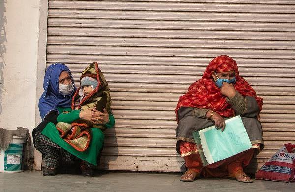 Kashmiri women wear face masks and wait outside a local hospital for treatment in Srinagar.