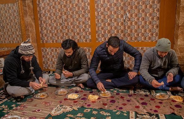 Kashmiri men eat 'Harisa' inside a shop early morning in Srinagar.