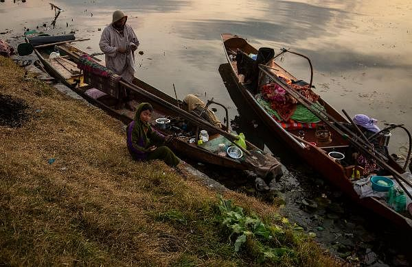 A Kashmiri fisherman's family have their boat anchored on the bank of the Dal Lake on a cold day in Srinagar.