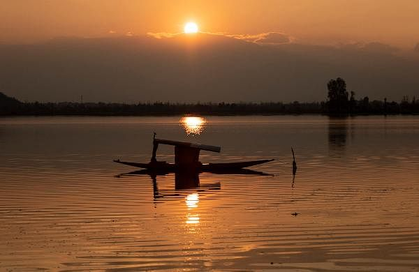 A boat is anchored on the middle of the Dal Lake as the sun sets on a cold day in Srinagar.