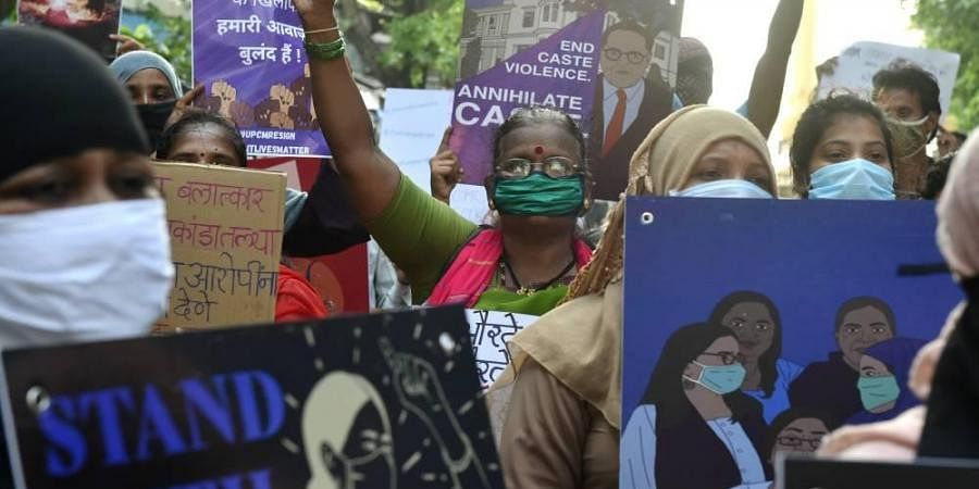 Activists hold placards and shout slogans during a protest against the death of Hathras gang rape victim.