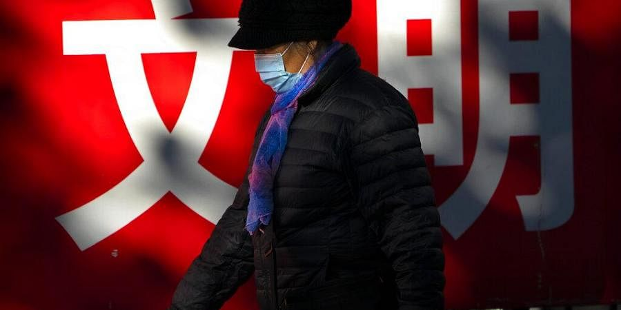 A woman wearing a face mask to protect against the coronavirus walks past a propaganda billboard with the characters for 'culture' in Beijing, Friday, Nov. 20, 2020.
