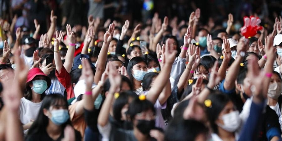A crowd flashes the three-finger protest gesture during a student rally in Bangkok Saturday, Nov. 21, 2020.