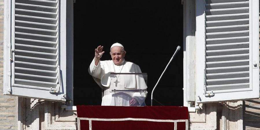 Pope Francis waves as he arrives for the Angelus noon prayer from the window of his studio