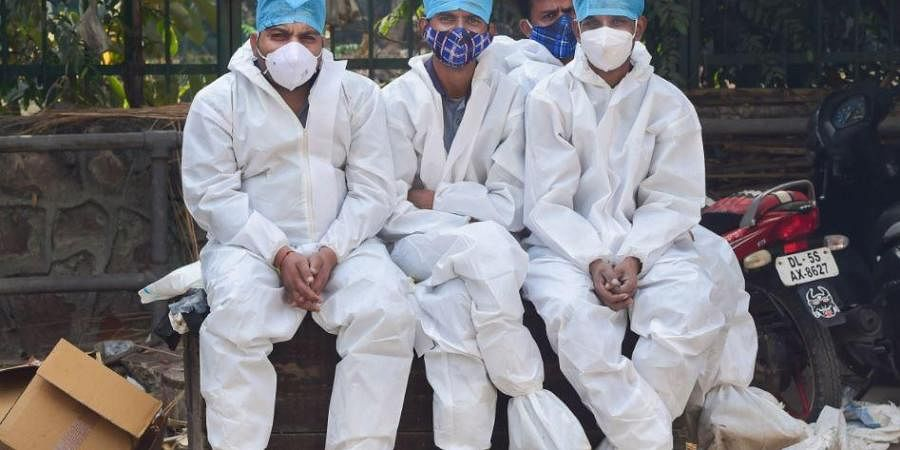 Workers wearing PPE take a break after cremating a person who succumbed to COVID-19, at Nigambodh Ghat in New Delhi