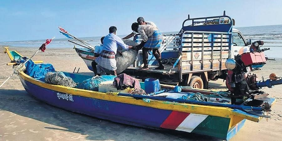 Fishermen shifting their nets and engines from a fiberglass boat to safe place in a coastal village near Vedaranyam.