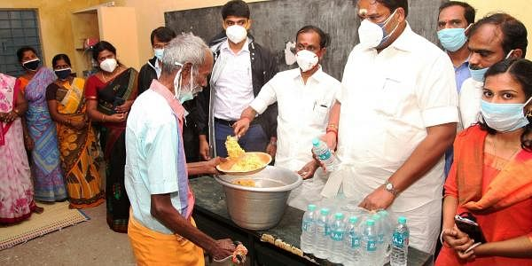 Tamil Nadu HR&CE Minister Sevoor S Ramachandran distributing food to evacuees at a temporary shelter in Kalasapakkam. (Photo| EPS)