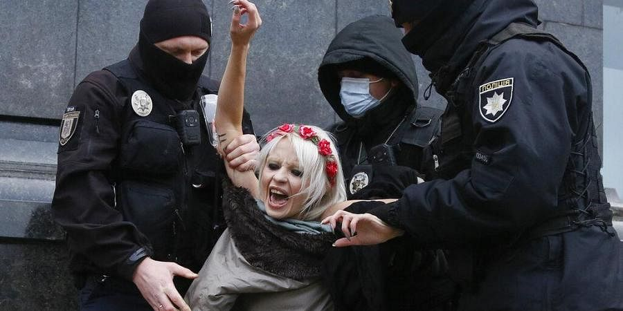 Police detain an activist from Ukrainian female rights organization 'Femen' on the International Day for the Elimination of Violence against Women as she protested naked