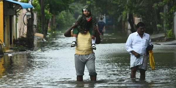 People make their way out of the homes on flooded road in Ram Nagar, Velachery, Chennai. (Photo | EPS/Ashwin prasath)