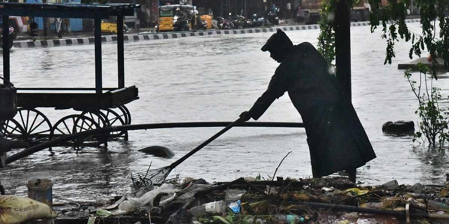 A corporation worker clearing the garbage for the free flow of flood Satyamurthy Nagar Thiruvatriyur following Nivar' on Wednesday in Chennai. (Photo | P Jawahar, EPS)