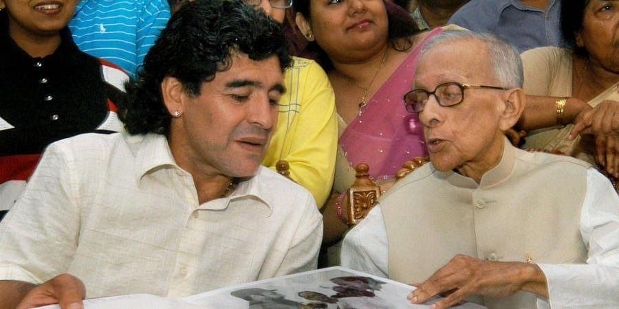 Football legend Diego Maradona of Argentina looks at a photo album with Veteran Communist leader Jyoti Basu during their special meet at the residence of Basu in Kolkata.