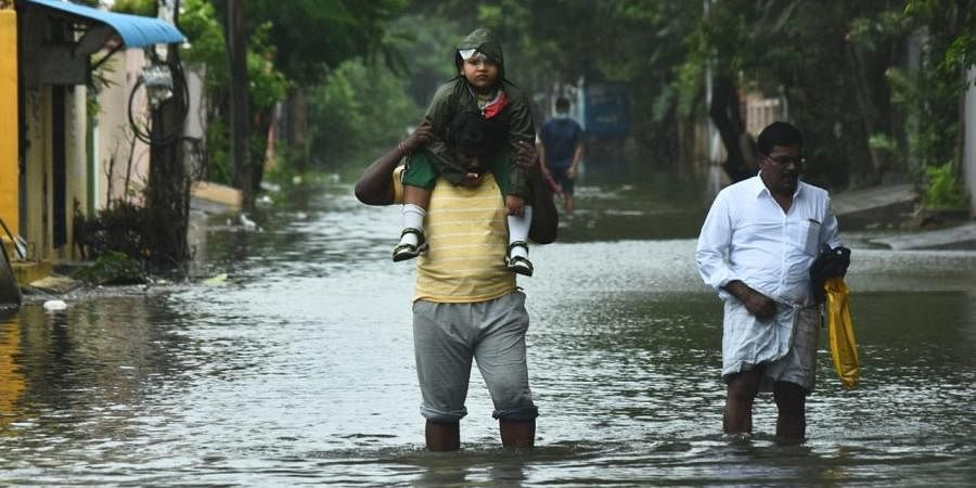 People make their way out of the homes on flooded road in Ram Nagar, Velachery, Chennai.