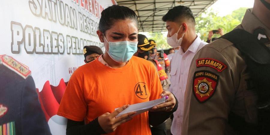 Instagram celebrity Millen Cyrus (C) is escorted by Indonesian police