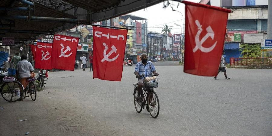 A man wearing mask as a precaution against COVID-19 pedals past flags of a Communist party trade union during a nation wide strike by various trade unions.