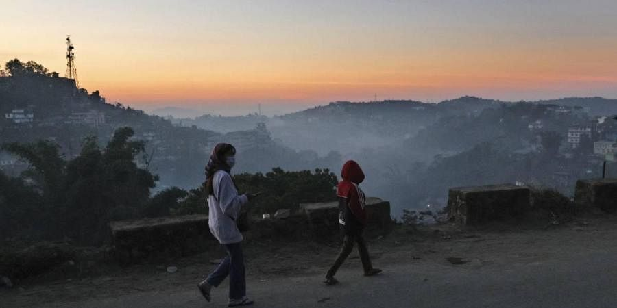 Nagas wearing face masks as a precautionary measure against the coronavirus walk on a road at sunset in Kohima, capital of Nagaland.