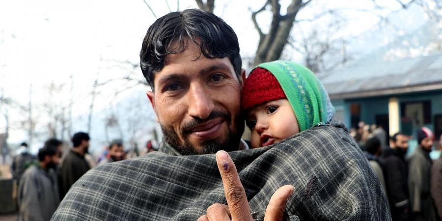 A man shows his inked finger after casting his vote for the first phase of District Development Council elections, in Srinagar