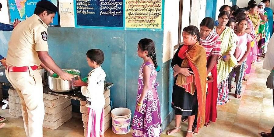 DSP B Sunil distributes food to the people lodged at a relief camp in Kadapa on Friday | Express