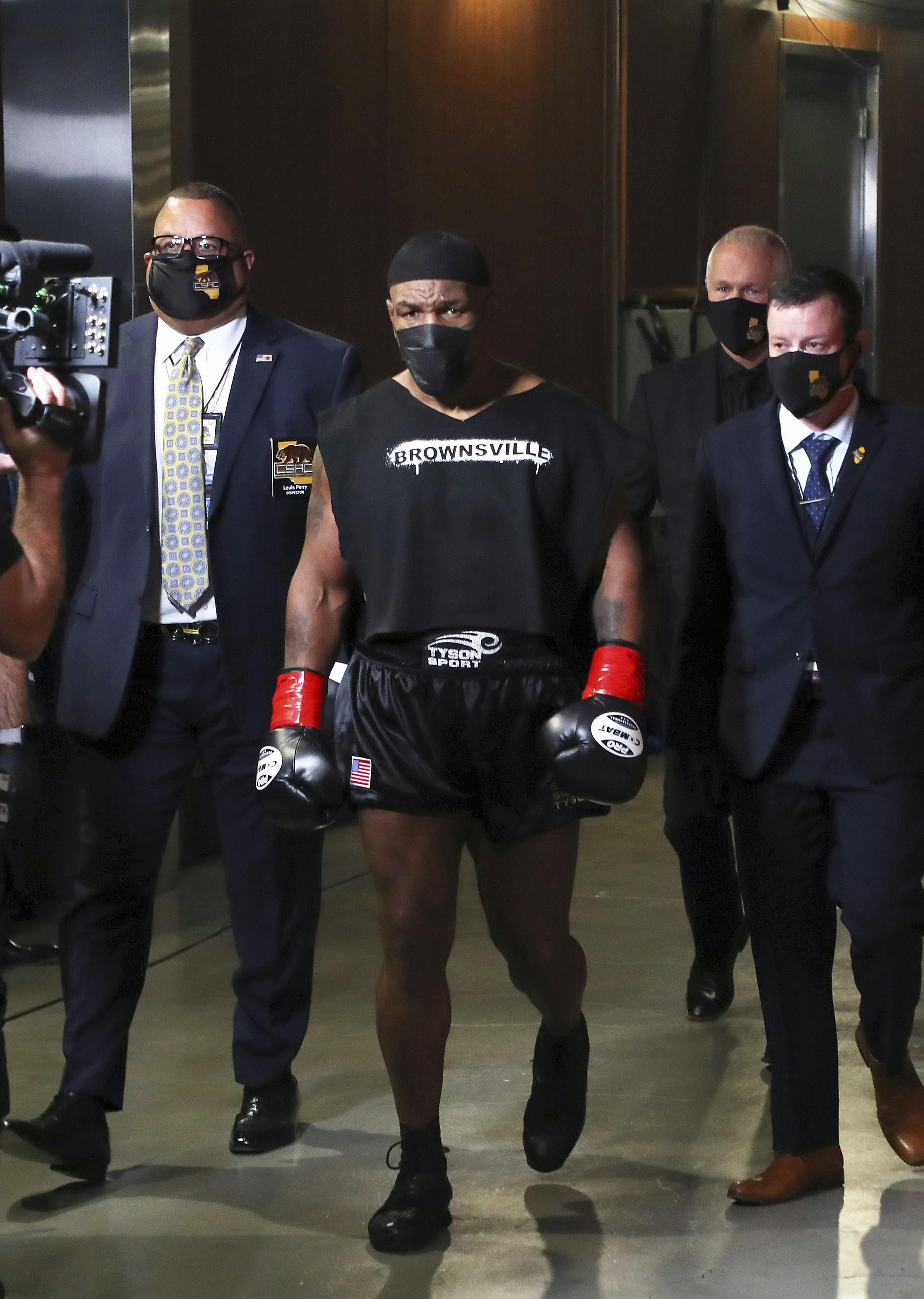 Mike Tyson (C) heads to the ring for an exhibition boxing bout against Roy Jones Jr in Los Angeles.